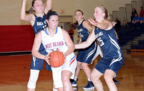 Photo courtesy of Jaclyn Yingling Herring gets rid of the ball as two opponents defend her.