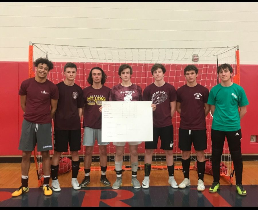 Altoona boys team holding up the bracket after winning the championship game