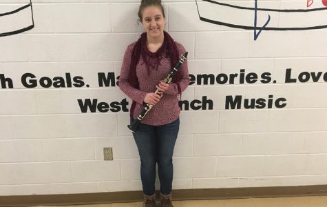 Regional Band Attendee Rachel Heitsenrether standing with her clarinet outside of the bandroom.