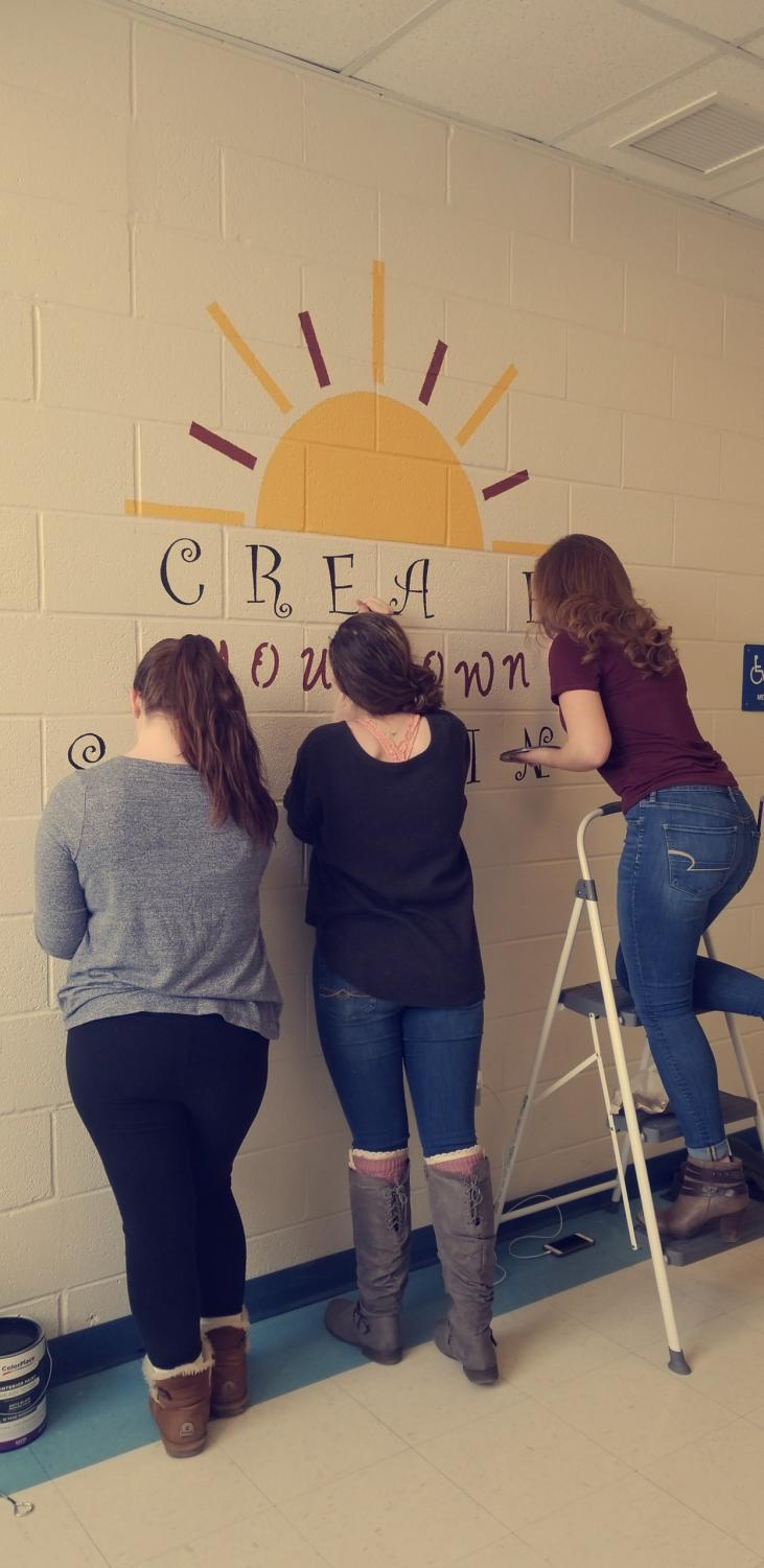 Shannae Fetterolf, Carolyn Folmar, and Dylanee Bell work on their inspirational wall art.