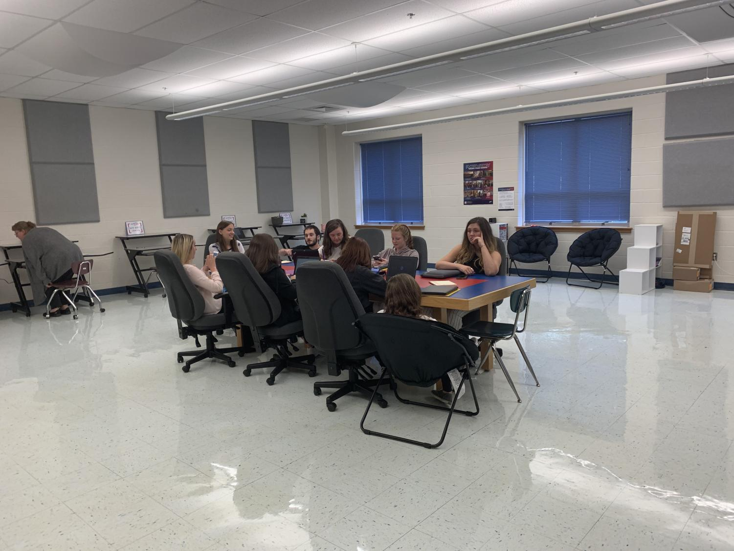 Journalism students discussing their new project in the multi-media room