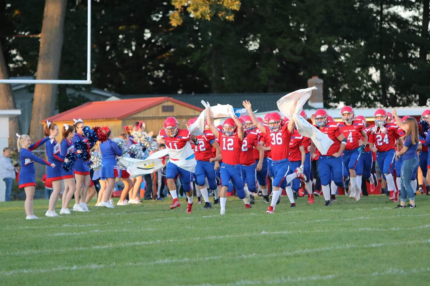 The Warriors run through the banner as the band plays