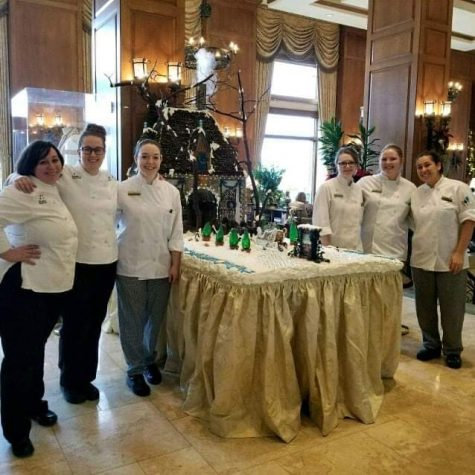 Aspen Galley and her coworkers pose for a photo in front of their artistic food creation