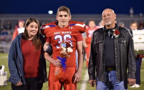 Aidan Kephart walking down the field on senior night escorted by his mom and grandfather.