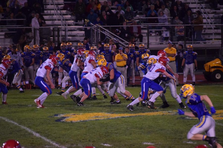 The Warriors and Blue-Devils clash at the line of scrimmage during last friday's contest.