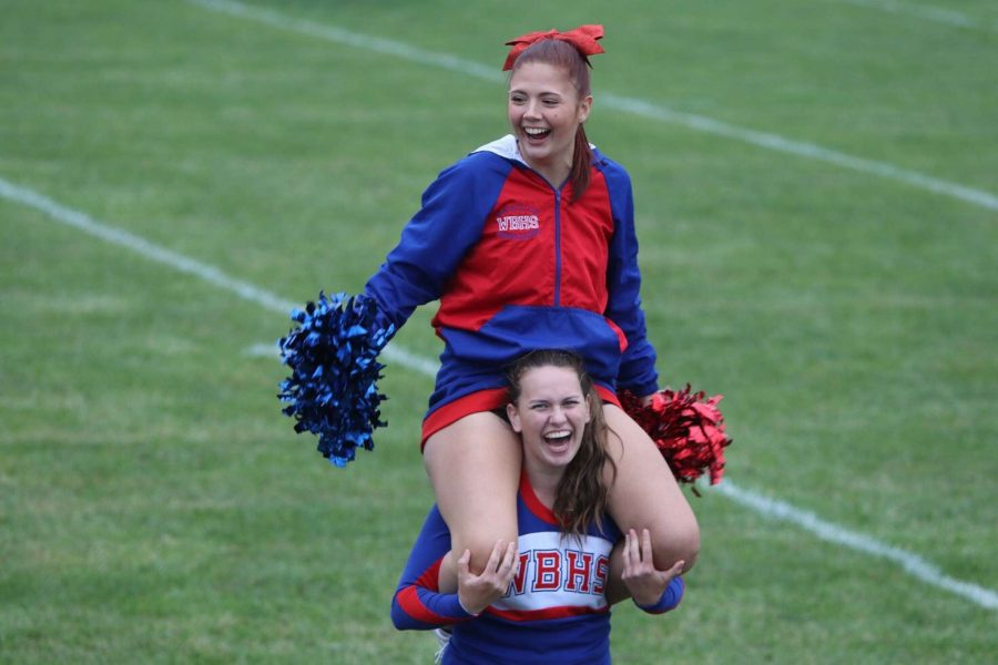 Senior Faith Zimmerman and Senior Taylor Maguire cheering at the football game