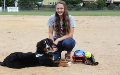 Ashley Mertz poses with her service dog, Tobie, at the softball field.