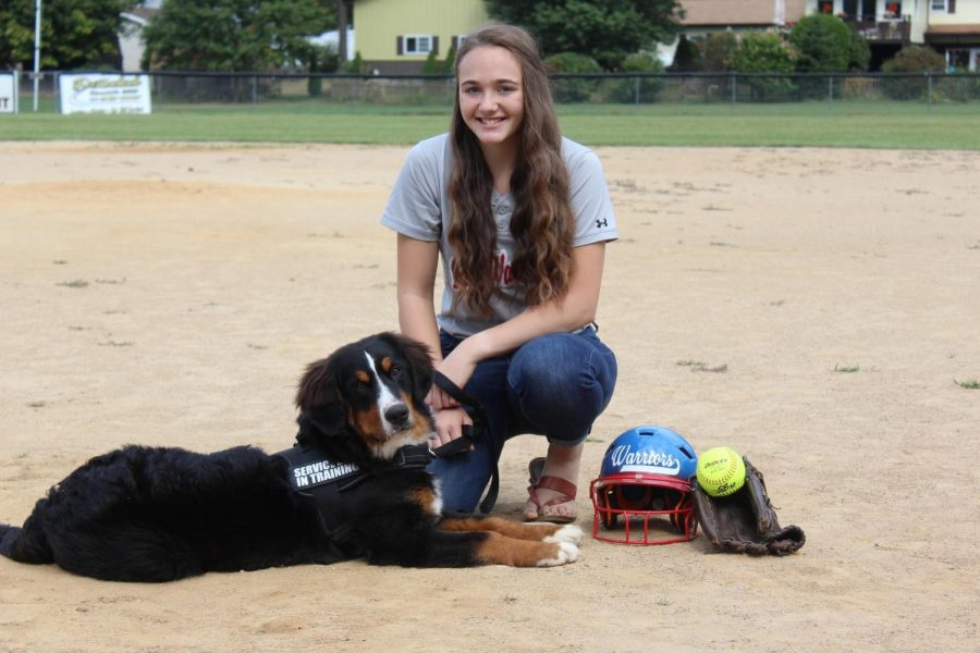 Ashley+Mertz+poses+with+her+service+dog%2C+Tobie%2C+at+the+softball+field.