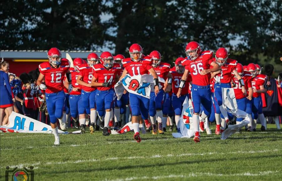 The Warriors run through their tunnel before the first game against Philipsburg.