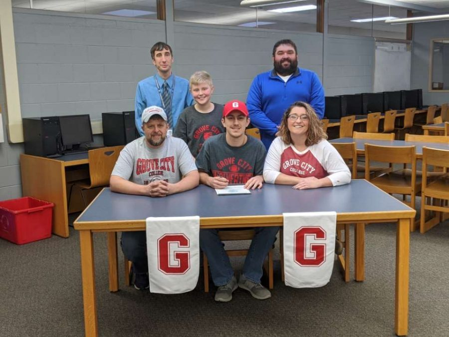 Ayden Gutierrez, surrounded by his family, Coach Hubler, and Mr. Williamson as he signs his letter of intent for Grove City College.