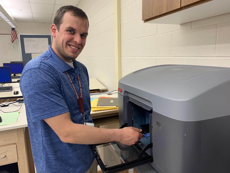Mr. Zimmerman using the 3D printing machine.