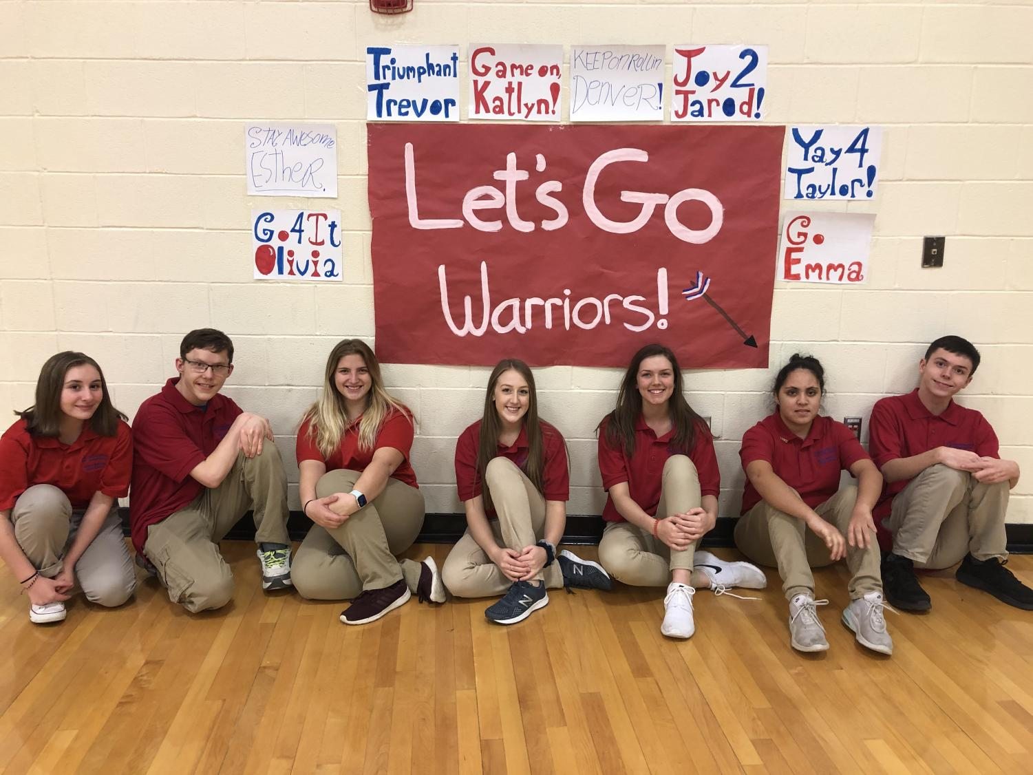 The West Branch Bocce Ball team sitting in front of fan posters.