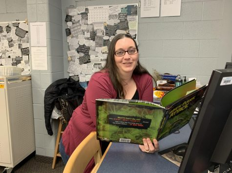 A photo of Ms. Folmar at her library desk, reading a book.