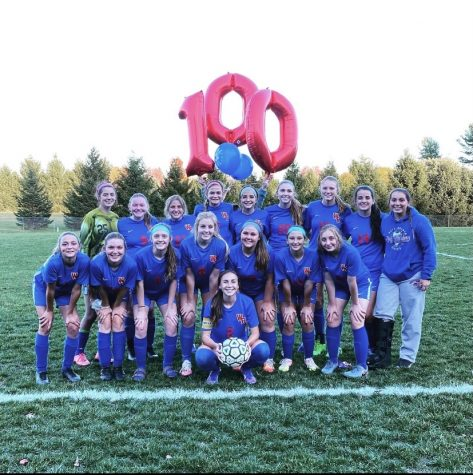 Lady Warriors posing for a picture with a 100 goal balloon