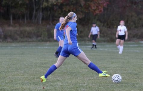 Anna Diviney dribbles the ball up the field looking for a pass.