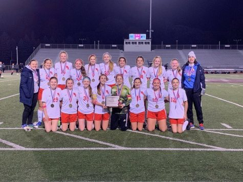 The Lady Warrior Soccer team smiles for a photo as captains Sarah Betts and Trinity Prestash hold the second consecutive District 6 title