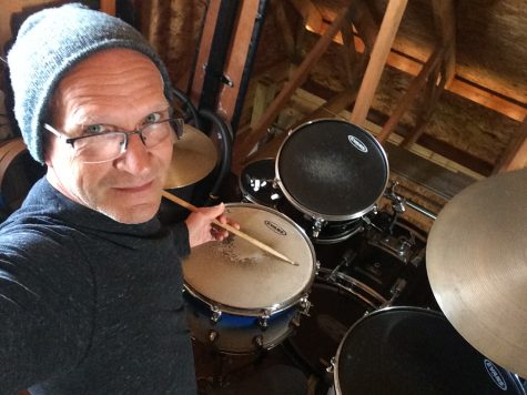 Mr. Hughes poses for a selfie at home with his drum set.