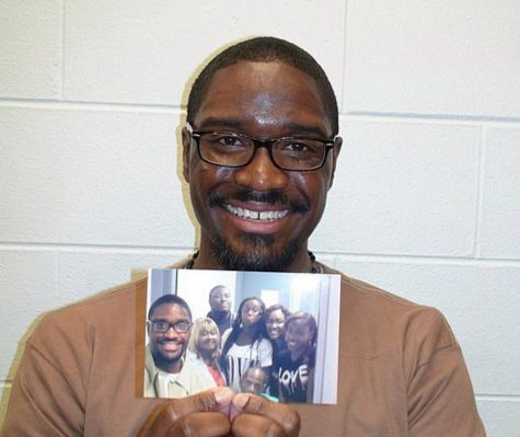 Brandon Bernard smiling while holding up a picture of his family.