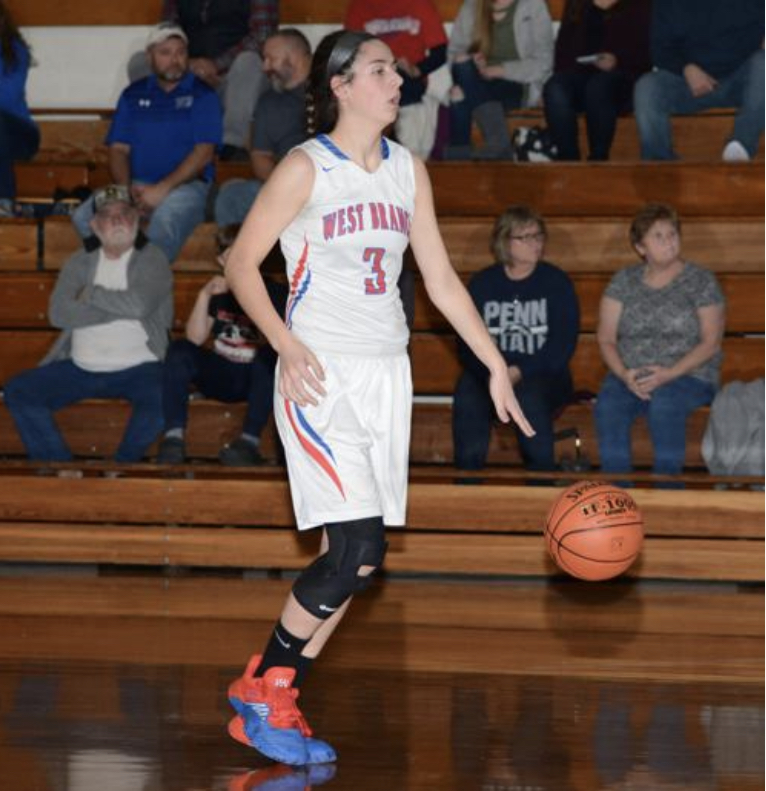 Sarah Betts dribbles the ball up the court while looking for a teammate to pass the ball to.