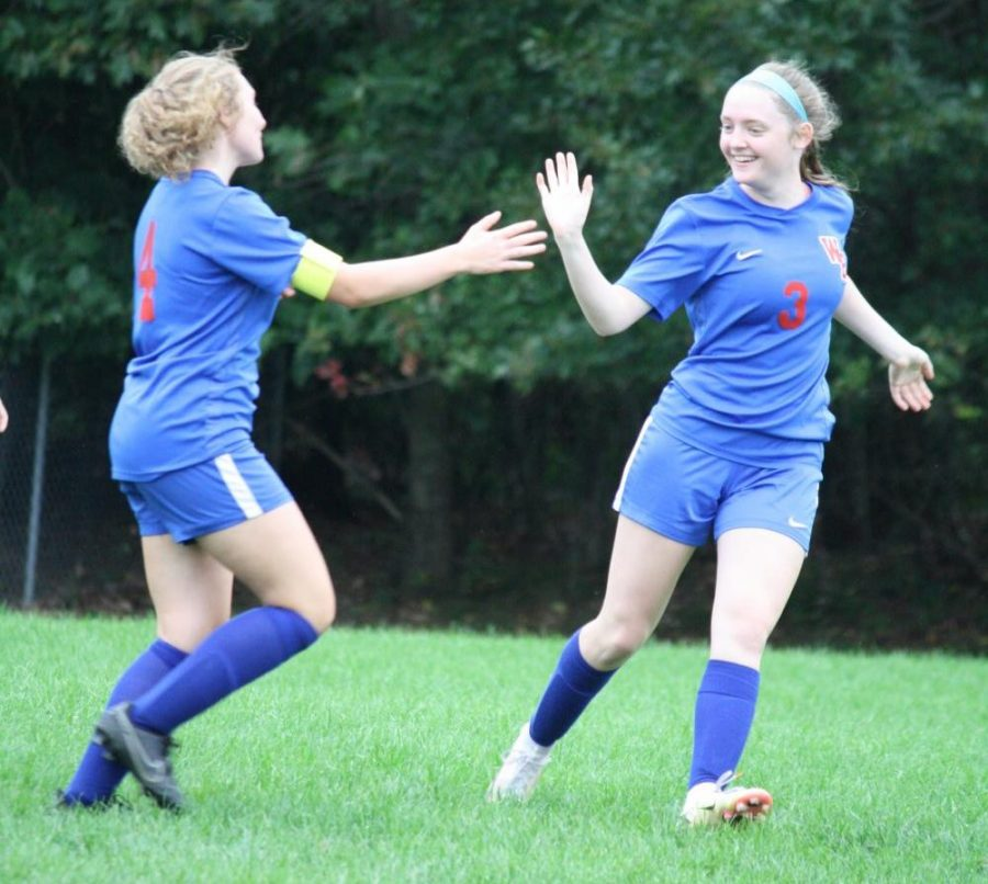 Olivia Stavola and Lauren Timblin go in for a high-five after a goal.